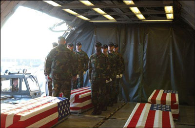 Flag draped coffins of soldiers killed in Iraq are being received on aircraft, while soldiers stand at attention.